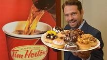 Actor Jason Priestley holds a plate of donuts in Oakville, Ont. on July 30, 2013. One lucky Canadian will have the chance to add their dream doughnut to the Tim Hortons menu and walk away with $10,000 as winner of Duelling Donuts contest, launched by the iconic bake shop today. T (The Canadian Press)