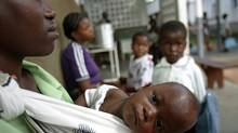 A mother waits with her child to be tested for malaria in Xai Xai, north of Maputo, in Mozambique on June 22, 2005. (ALEXANDER JOE/ImageForum)