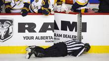 NHL linesman Don Henderson lies face down on the ice after being struck from behind by Calgary Flames defenceman Dennis Wideman on Jan. 27, 2016. (Jeff McIntosh/The Canadian Press)