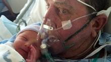 Mark Aulger, holds his one-day-old daughter, Savannah, at a hospital in Plano, Tex. (Diane Aulger/AP)