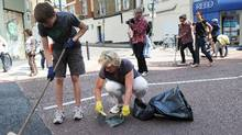 Members of the public sweep the streets in Clapham Junction, in south London, on August 9, 2011, of debris following a third night of unrest in London. (PAUL ELLIS/AFP/Getty Images)