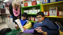 Robyn Thiessen works with students Mehar Shergill, 10, middle, and Kabir Sidhu, 10, at Green Timbers Elementary School in Surrey, B.C., on Jan. 9, 2014. (Rafal Gerszak for The Globe and Mail)