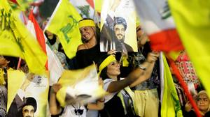 Lebanese Hezbollah supporters wave the movement's yellow flag alongside their national flags in southern Beirut as the group's leader Hassan Nasrallah delivers a televised address.