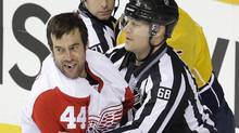 Detroit Red Wings right wing Todd Bertuzzi is led to the penalty box by linesman Scott Driscoll after Bertuzzi fought with Nashville Predators defenceman Shea Weber in the first period of Game 2 of an NHL hockey Stanley Cup first-round playoff series, Friday, April 13, 2012, in Nashville. (Mark Humphrey/Associated Press)