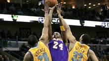 Los Angeles Lakers guard Kobe Bryant (24) pulls up a jump shot over New Orleans Hornets center D.J. Mbenga (28) and guard Willie Green (33) during the first half of their NBA basketball game in New Orleans, Louisiana February 5, 2011. (MISTY MCELROY)