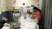Hassan Rasouli, who is in vegetative state at Sunnybrook Hospital, is shown family photos by daughter Majgan and wife Parichehr Salasel at a Toronto hospital. (Fernando Morales/The Globe and Mail)