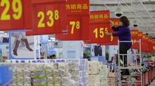 A worker adjusts a price tag at a supermarket in Wuhan, Hubei province, Nov. 9, 2012. China's annual consumer inflation eased to 1.7 per cent in October from September's 1.9 per cent, official data showed on Friday, leaving policy makers with some scope to tweak monetary policy if necessary to shore up growth. (DARLEY SHEN/REUTERS)
