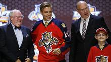 Aaron Ekblad stands with Florida Panthers officials after being chosen first overall during the first round of the NHL hockey draft, Friday, June 27, 2014, in Philadelphia. (Associated Press)