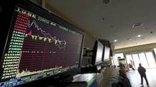 An electronic board showing stock information is seen above investors at a brokerage house in Wuhan, Hubei province January 4, 2012. China shares started the new year weaker on Wednesday, dragged down by more cyclical sectors after the Chinese premier warned of difficult economic conditions in the first quarter, hinting there will not be another massive fiscal stimulus program. (Reuters)