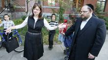 Mindy Pollak, left – a member of Montreal's ultra-Orthodox Hasidic Jewish community who is running for office in the city's fall election – speaks with resident Eli Herzog as she canvasses door to door in Outremont on Aug. 20, 2013. (CHRISTINNE MUSCHI FOR THE GLOBE AND MAIL)