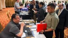 A job fair attendee talks with James Echeverry of Queens at Choice Career Fairs' New York career fair. (Craig Warga/Bloomberg)