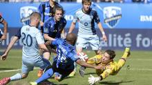 Montreal Impact goalkeeper Troy Perkins (1) makes a save as Sporting KC midfielder Oriol Rosell (20) and Montreal Impact midfielder Collen Warner (18) look on during the first half at Stade Saputo. (Eric Bolte/USA Today Sports)