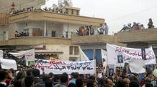 In this citizen journalism image made on a mobile phone and acquired by the AP, Syrian protesters carry banners in Arabic and Kurdish that call for a democratic nation as they demonstrate in the northeastern town of Qamishli, Syria, Friday, April 29, 2011. (STR/The Associated Press)