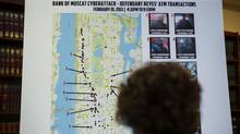 A woman looks at a map showing where eight members belonging to a New York-based cell of a global cyber criminal organization withdrew money from ATM machines, during a news conference in New York, May 9, 2013. (LUCAS JACKSON/REUTERS)