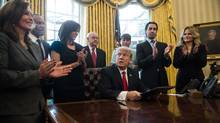 U.S. President Donald Trump reacts after signing an executive order with small business leaders in the Oval Office of the White House in Washington, DC, on January 30, 2017. (NICHOLAS KAMM/AFP/Getty Images)