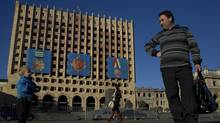 People pass by the Council of Ministers of Abkhazia building destroyed during the 1992-1993 military conflict in Sukhumi, the capital of Georgia's breakaway region of Abkhazia December 25, 2013. (Maxim Shemetov/REUTERS)