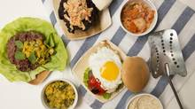 Three types of burgers, Malaysian, at left with lettuce; Peruvian, centre, with egg and roasted pepper; and Korean, topped with kimchi, top. (Peter Power for The Globe and Mail)