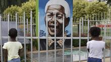 Children look through a fence at a portrait of former president Nelson Mandela in a Park in Soweto, South Africa, March, 28, 2013. 94-year-old Mandela, the anti-apartheid leader who became South Africa's first black president, has been hit by a lung infection again and is in a hospital, the presidency said. (Denis Farrell/AP)