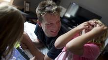 "Tim Kelloway spends time playing and reading with his children at their Toronto home on June 7, 2012. Daughter Suri, 4, gets a real laugh out of calling her dad ""momma."" (Peter Power/The Globe and Mail)"
