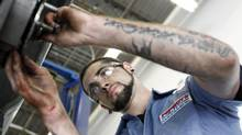 Technician Chris Shannon works on a costumers car at a Pep Boys Auto retail and service location, in Philadelphia in this file photo. (Matt Rourke/AP)