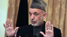 Afghanistan's President Hamid Karzai talks during a press conference at the presidential palace in Kabul on November 23, 2010. Afghan President Hamid Karzai denied meeting a purported top Taliban negotiator, who may have been an imposter. (MASSOUD HOSSAINI/MASSOUD HOSSAINI/AFP/Getty Images)