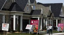 People walk past new homes that are for sale in Oakville, Ont. (NATHAN DENETTE/Nathan Denette/The Canadian Press)
