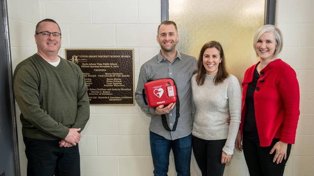 Rich Perverly, centre, visits a school as part of his campaign to raise money to put automatic external defibrillators (AEDs) in schools and to train young people how to use them.