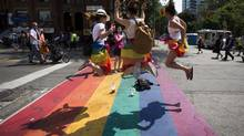 "Revelers jump on a rainbow painted crosswalk in Church Street, Toronto's LGBT neighbourhood, before "" WorldPride"", a gay pride parade, in Toronto, June 29. (MARK BLINCH/REUTERS)"