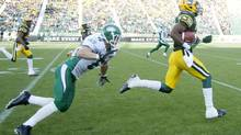 Edmonton Eskimos' Marcell Young (23) runs for a touchdown as Saskatchewan Roughriders' Rob Bagg (6) chases during first half preseason action in Edmonton, Alta., on Friday June 14, 2013. (JASON FRANSON/THE CANADIAN PRESS)