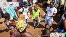 A health worker volunteer talks with residents on how to prevent and identify the Ebola virus in others, and distributes bars of soap in Freetown, Sierra Leone, Saturday, Sept. 20. (Michael Duff/AP)