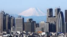 Mount Fuji looms over the Tokyo skyline. This week, Japan reported its first annual trade deficit since 1980, caused by the impact of the March 11 earthquake, tsunami and energy crisis and a decline in exports attributable in part to the strong yen. (Associated Press/Associated Press)