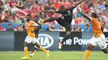 Toronto FC's Jermain Defoe, centre, leaps for a ball during the first half of MLS soccer action against the Houston Dynamos in Toronto. (Darren Calabrese/The Canadian Press)