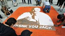 People pay their respects as they write messages on the sidewalks and a banner remembering late NDP leader Jack Layton at Toronto City Hall on Aug. 26, 2011. (Nathan Denette/THE CANADIAN PRESS)