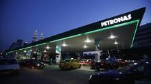 Motorists queue to fill natural gas at a Petronas station with its landmark Petronas Twin Towers headquarters in the background, in Kuala Lumpur Feb. 4, 2012. (© Bazuki Muhammad / Reuters/REUTERS)