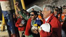 Luis Urzua, the last miner to be rescued, cheers with Chilean President Sebastian Pinera at the mouth of the San Jose mine on Oct. 13. (HO/Reuters)