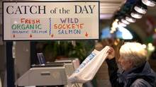 A shopper buys fresh fish at St. Lawrence Market in Toronto. (J.P. Moczulski)
