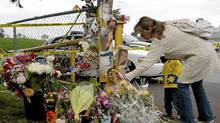 A mother and son place a memento at the memorial of slain teen Laura Szendrei on Oct. 8, 2010, in Delta, B.C. (Lyle Stafford for The Globe and Mail)