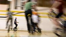 A group of unicyclists get practice at their art while playing a game of unicycle basketball at St. Josaphat Catholic School  on Pelham Avenue in Toronto on March 26, 2012. The group  (www.torontounicyclists.ca) practices on Tuesday evenings. (Peter Power/The Globe and Mail)