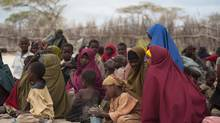 Mothers sit with their children in a compound for internally displaced persons (IDPs) in the Somali border town of Dhobley on August 11, 2011, 100 km from Dadaab refugee complex. (PHIL MOORE/AFP/Getty Images)