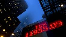 The head offices of Canada's biggest banks are shrouded in fog and cloud as a sign board display's the final closing number of the year for the TSX of Friday December 30, 2011. (Frank Gunn/The Canadian Press)