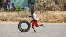 A young boy rolls a used tire in Harare, Zimbabwe July 27, 2012. Zimbabweans from all walks of life are drowning in debt after the implosion of a three-year credit bubble. (TSVANGIRAYI MUKWAZHI/AP)