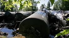 Rail cars leak bunker fuel oil metres from summer homes bordering Lake Wabamun after a freight train derailed on Aug. 3, 2005. (JOHN ULAN/The Canadian Press)