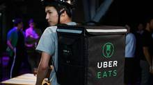An employee poses for a photograph at a launch event for the UberEats delivery service in Tokyo. (Akio Kon/Bloomberg)