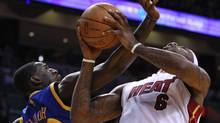 Golden State Warriors Ekpe Udoh (L), fouls the Miami Heat's LeBron James during first quarter in NBA basketball action in Miami January 1, 2011. REUTERS/Hans Deryk (HANS DERYK)