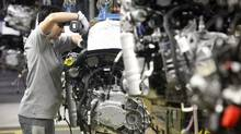 A worker assembles an engine at the Magna Steyr factory site in Graz. (Herwig Prammer/Reuters)