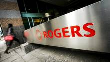 A woman walks past a Rogers sign on the day of the Rogers Communications Inc. annual general meeting for shareholders in Toronto, April 21, 2015. (MARK BLINCH/REUTERS)