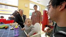 Adam, left, and Katja Thom, check in with one of the young patrons of the popular drop-in centre at 826 Bloor St. W. (Deborah Baic/The Globe and Mail)