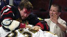In this Oct. 28, 2001 file photo, Chicago Blackhawks' Bob Probert, left, and Boston Bruins' Andrei Nazarov mix it up along the boards during a first period fight in Chicago. Enforcers, goons, whatever you want to call them, players like Bob Probert and Derek Boogaard made careers from dishing out and taking punishing hits. That job is sure to come under added scrutiny after the sudden death of Boogaard, five months after he suffered a season-ending concussion.(AP Photo/Fred Jewell, File) (Fred Jewell/AP)