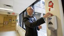Dr. Michael Gardam, Director, Infection Prevention and Control with the University Health Network, shows a hand washing sign developed by a cardiologist and a red tag on a hand sanitizer dispenser, that when up shows it needs refilling at The Toronto General Hospital in Toronto on May 29, 2013. (Deborah Baic/The Globe and Mail)