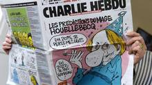 A person reads the latest issue of the French satirical newspaper Charlie Hebdo in Paris on January 7, 2015. (BERTRAND GUAY/AFP/Getty Images)